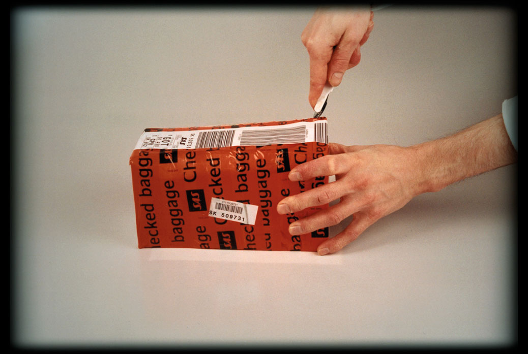 The Trip To America, film still, paper box covered in tape labelled Checked Bagage is being opened by a knife.