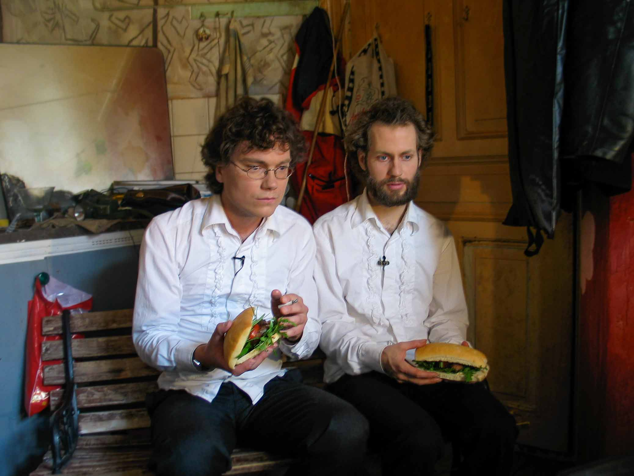 Cuisine Bizarre, video still, Frans Einarsson and Björn Perborg with sandwiches and cigarette.