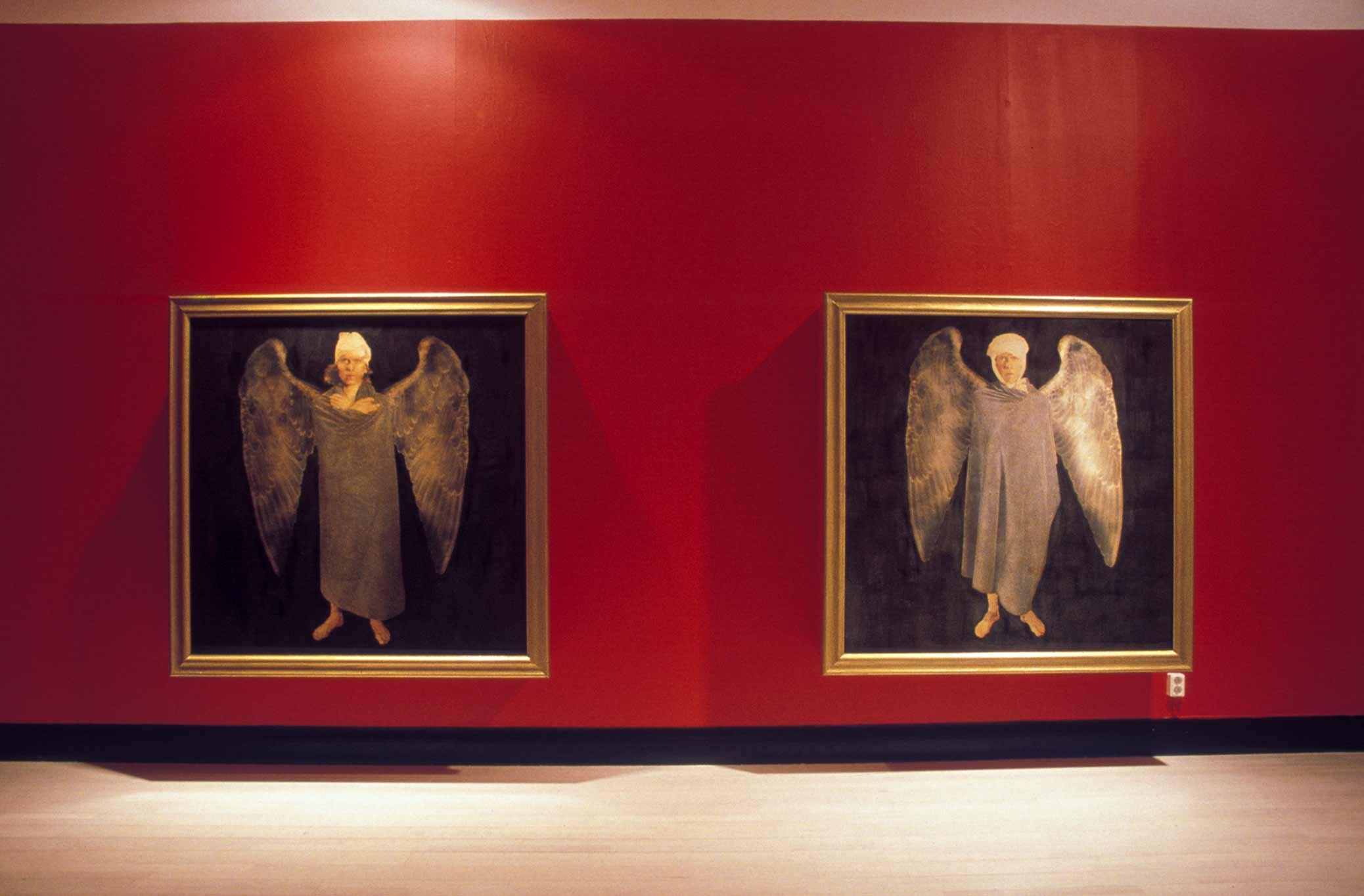 Flygfän, installation with paintings of wounded angels, in a room with red walls. Flygfän, installation med tavlor föreställande skadade änglar, i ett rum med röda väggar.