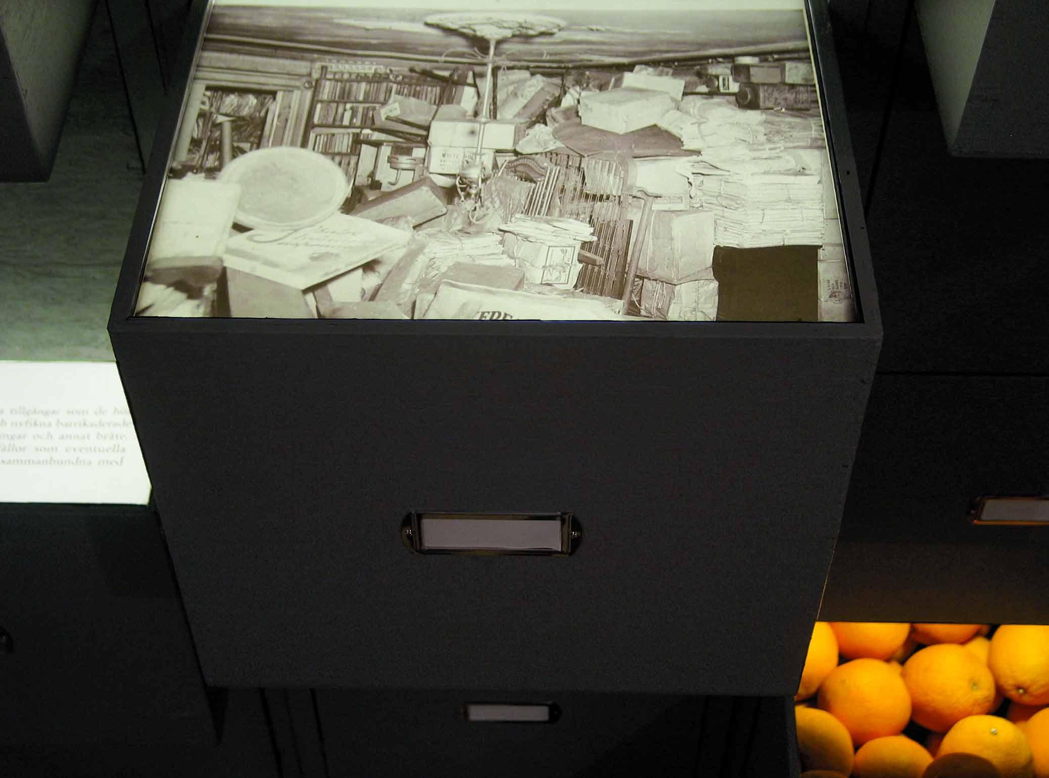 Samlarna, installation med arkivskåp på Galleri Box. Detalj, arkivfoto och apelsiner.