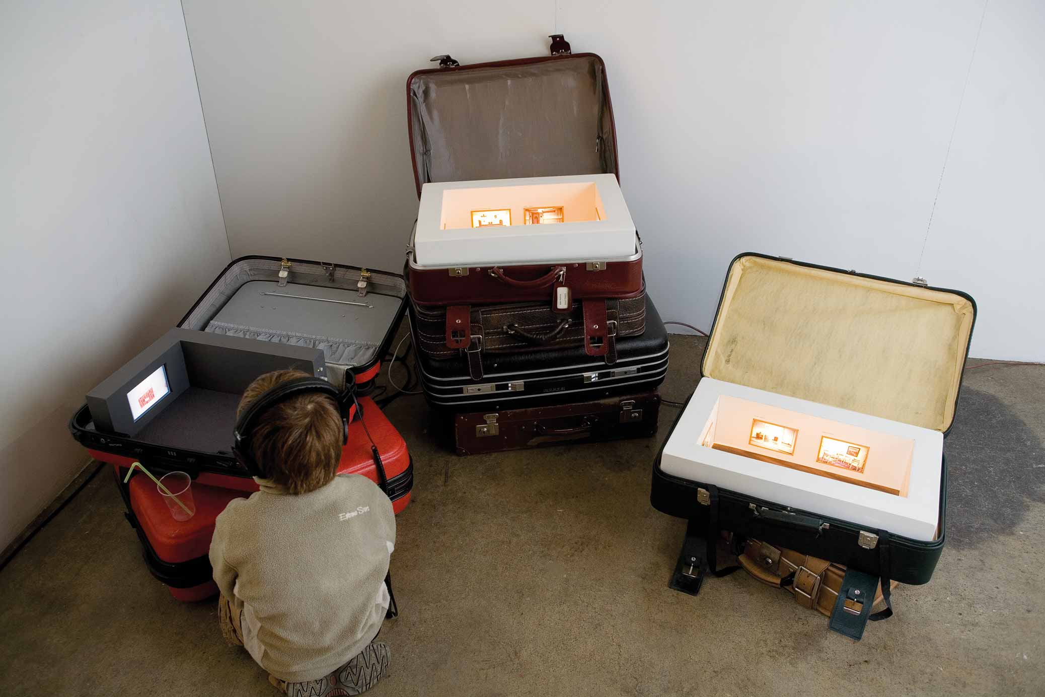 Suitcase Studies, installation with miniature exhibitions inside suitcases. Boy watching video.
