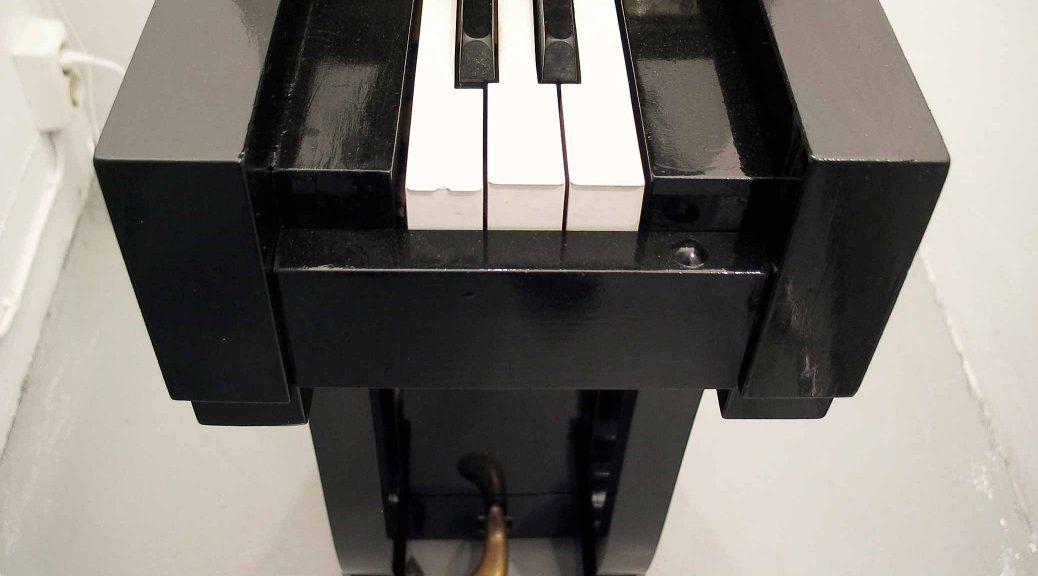 Piano, narrow piano with three white and two black keys, sculpture by Björn Perborg, detail. Piano, smalt piano med tre vita och två svarta tangenter, skulptur av Björn Perborg, detalj.